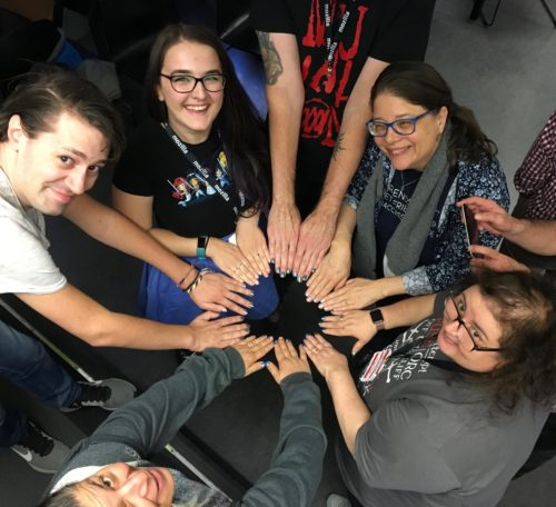 A circle of people showing their painted nails and looking at the camera
