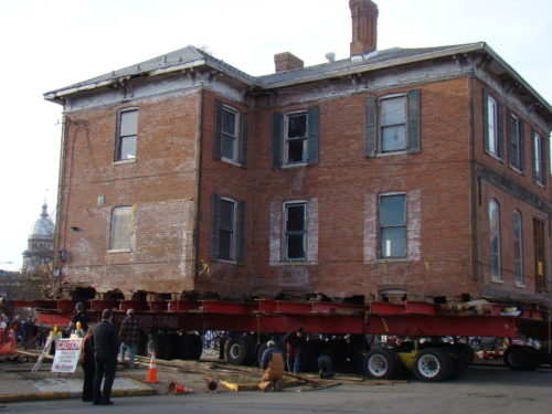 A two-story, 19th-century building, loaded on 64 wheels, is moved down a street by a dozen workers in hardhats